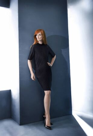 clothing: Redhead model wearing dress in studio Stock Photo