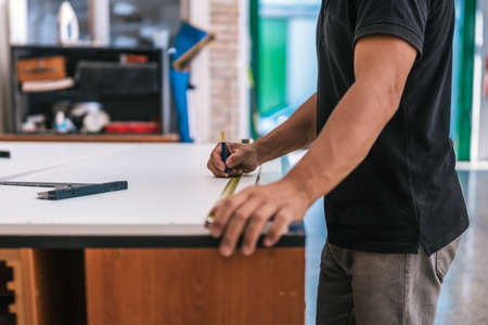 Hand of a man using a pencil to mark a measured point on a surface in a workshop
