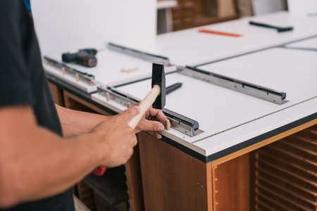 Man nailing a wooden stud with a hammer to a surface of a furniture in a workshop Banco de Imagens