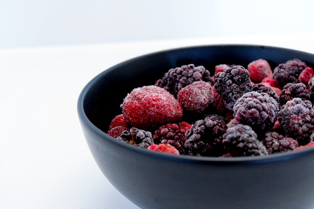 icey: Frozen Berries in black bowl on white surface Stock Photo