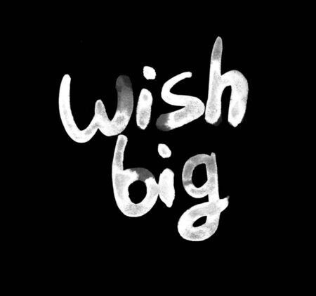 Wish big white watercolor lettering drawn in chalk on a chalk board.