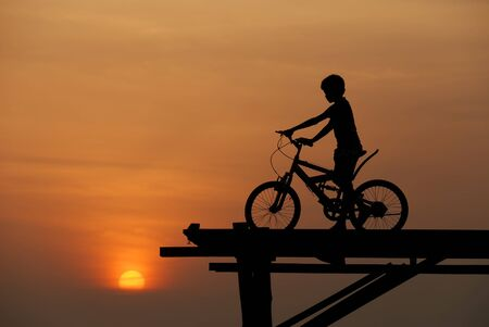 bicycle silhouette: boy on bike sunset