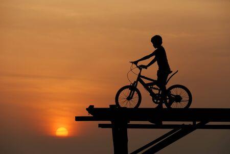 ciclo del agua: Boy on sunset de bicicleta
