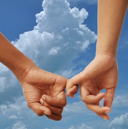 couple holding hands: male and female hand  sign of love with cloudy sky background