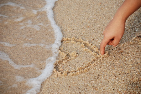 heart drawing on the sand with nice lady hand photo