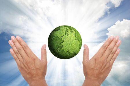 concept of green globe on shining beam sky. photo