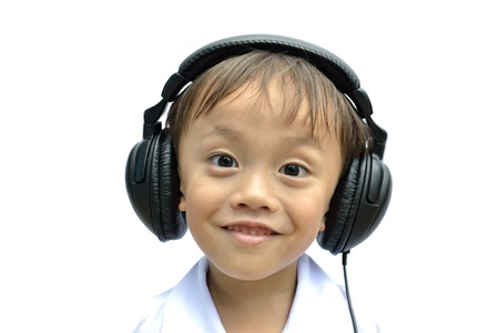 cute asian young boy using headphone on white background. photo