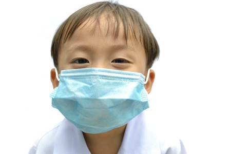 cute asian young boy wearing disposable face mask on white background. photo