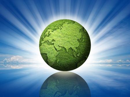 environment saving idea by grass globe on blue sky. photo