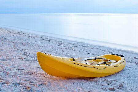 single yellow kayak on thebeach at twilight.