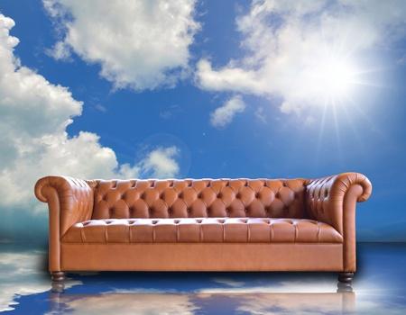 Single vintage style sofa on blue sky background. photo