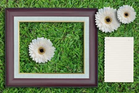 Marco de fotos en blanco con el papel en blanco sobre fondo de hierba. photo
