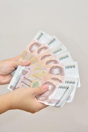 woman han holding one thousand thai baht banknotes. photo