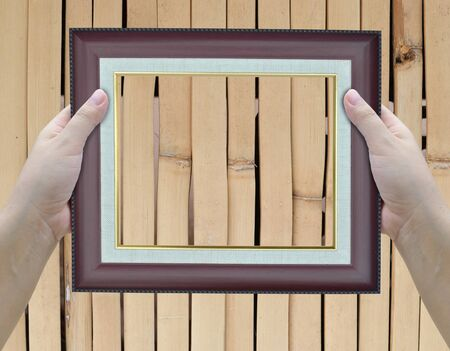 artwork of two hands holding picture frame. photo