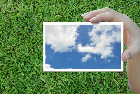 sky picture in woman hand over nice background. photo