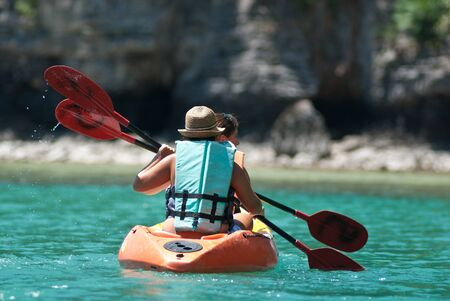 traveler kayaking in the thai ocean from backward view