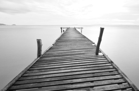 balck and white picture of old bridge to the sea. Stock Photo