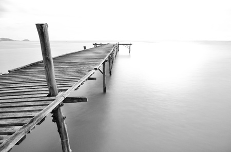 balck and white picture of old bridge to the sea. photo
