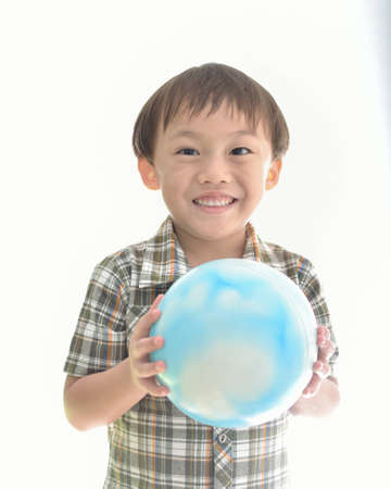 Cute asian boy with globe on white background. photo