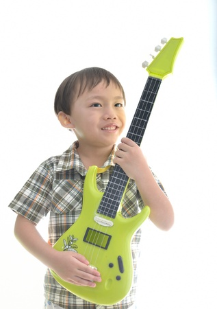 Cute asian boy with private guitar on white background. Stock Photo - 12606825