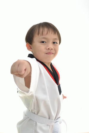 Cute asian boy with taekwondo uniform on white background. photo