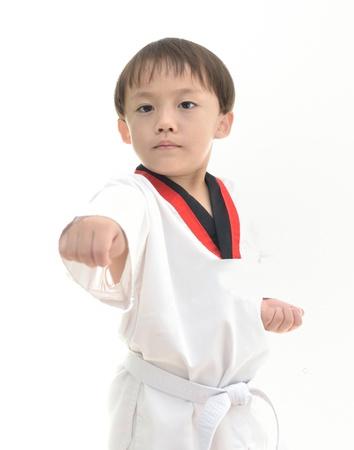 Lindo chico asiático con el uniforme de taekwondo en el fondo blanco. Foto de archivo - 12606748