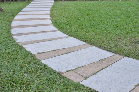Curve of cement walk path with grass field background. photo