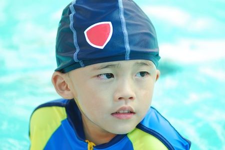 Cute young boy in swimming suit in the pool. photo