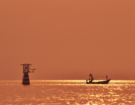 Sunrise view with small boat and golden sky. photo