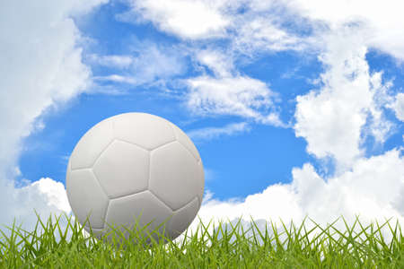 Blank white football on grass field with sky background. photo