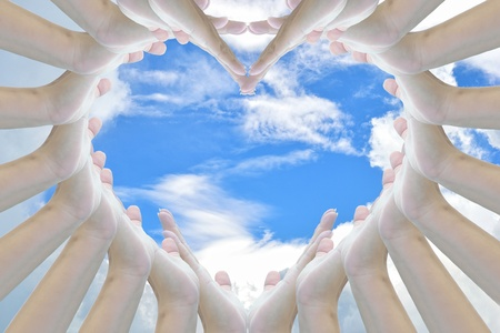 Heart sign from woman hand on sky background. photo