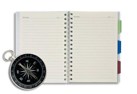 Classic compass on open blank notepad background. photo