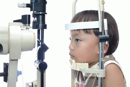 fundus: Small boy with slit lamp microscope for eye examination. Stock Photo