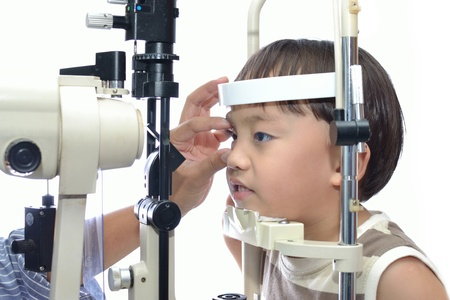 astigmatism: Small boy with slit lamp microscope for eye examination. Stock Photo