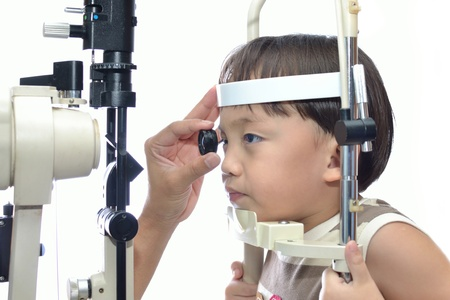 eye test: Small boy with slit lamp microscope for eye examination. Stock Photo