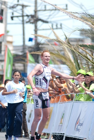SAMUI, THAILAND - APRIL 22 2012: Samui triathlon 2012 event. Overall champion David Dellow in action during finish the triathlon on Sunday 22 April 2012 in Ko Samui island, Suratthani, Thailand.