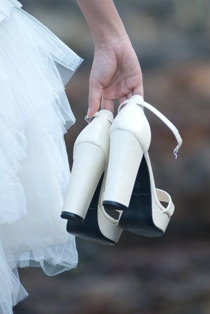 Shoes in bride hand with pre wedding sceen out door bckground. Stock Photo - 13371154