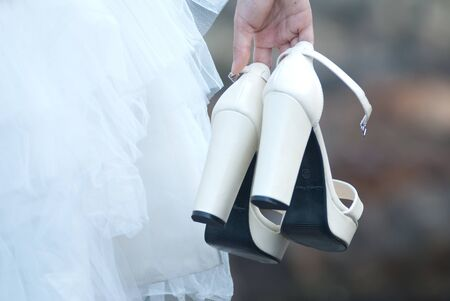 Shoes in bride hand with pre wedding sceen out door bckground. Stock Photo - 13371080