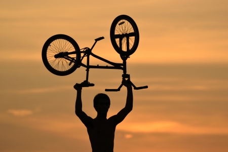mountainbike: bmx rider action against sky at sunset.