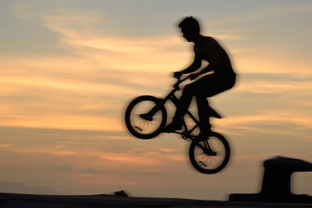 l'action pilote bmx contre le ciel au coucher du soleil. photo