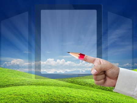 business education by business hand with red pencil tip of index over nature background. photo