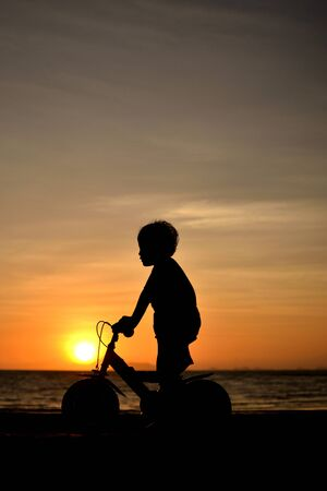 silhouette of small boy on bike at dusk. Stock Photo - 14868060