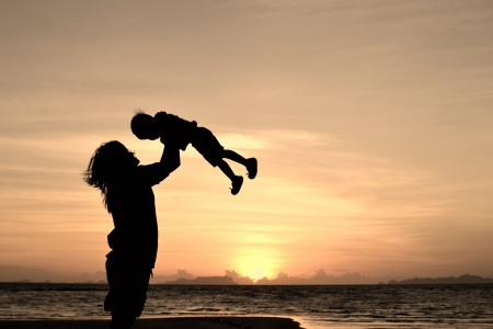 silhouette of mommy and small girl on the beach at dusk. photo