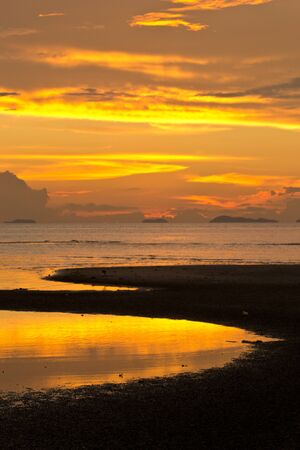 Golden sky during sunset at the beach. photo