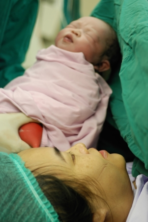 New born infant from cesarean section in operating theater.