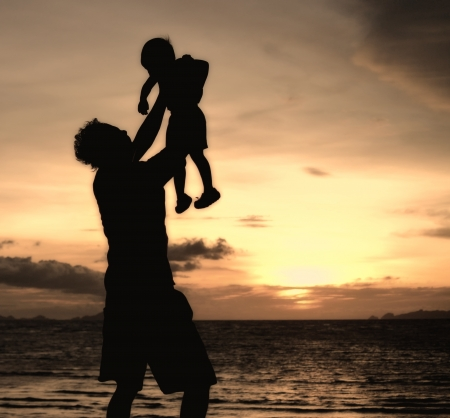silhouette of daddy and small girl on the beach at dusk. photo