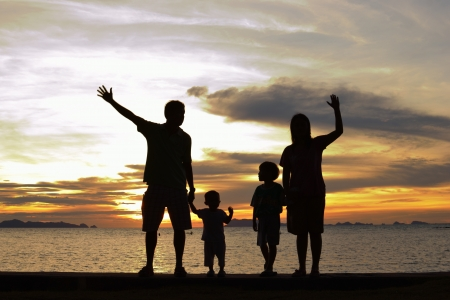 silhouette of family on the beach at dusk. photo