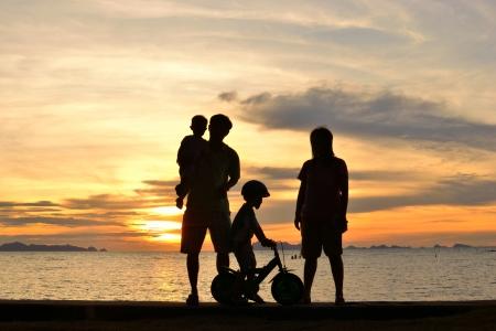 pique nique en famille: silhouette de la famille sur la plage au coucher du soleil.