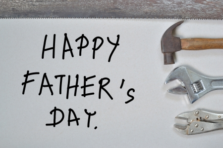 pounding head: happy fathers day with house tools over grey  background.