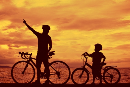 Biker family silhouette , daddy and son at the beach at sunet. photo